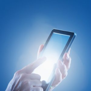 A finger touching a glowing smartphone