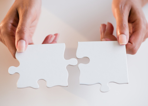 A woman holding two puzzle pieces