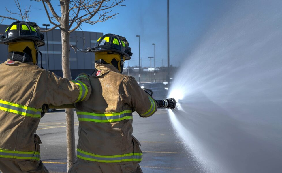 two fire fighters with a hose