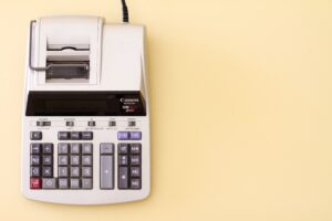 An adding machine on a yellow background