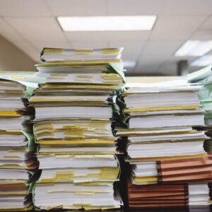 A stack of files piled high on a desk